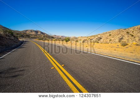 Long diagonal road with sand alongside through the Mojave desert of California