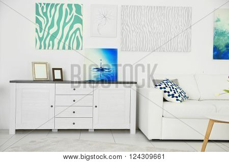Modern living room interior with white sofa, lockers and canvases on the white wall