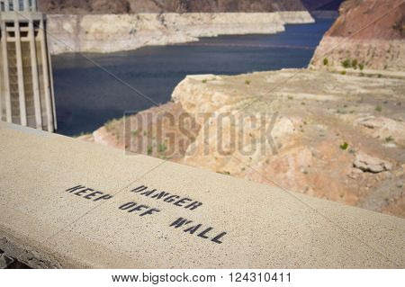 Warning on the edge of the Hoover Dam keeps people from climbing on the dam wall.