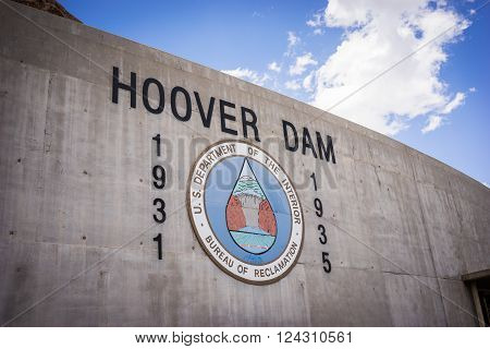 Logo and sign on the side of the Hoover Dam site in southwest United States.