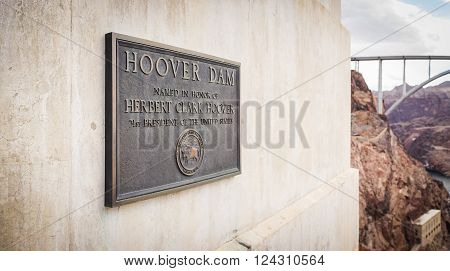Metal sign honoring Herbert Hoover hangs from the side of a dam building.