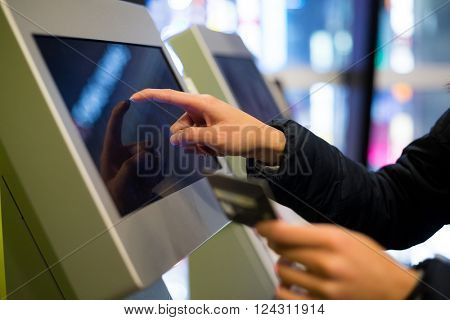Woman using credit card to pay on the automatic cinema ticketing terminal