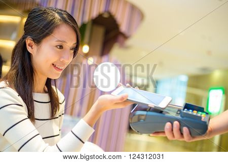 Woman pay with mobile phone by NFC technology