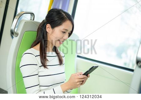 woman using cellphone inside train compartment