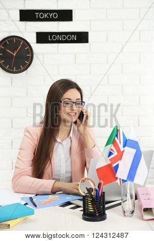 Young woman talking on the smart phone in the office of travel company