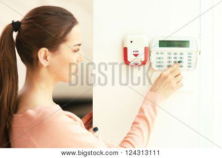 Woman pressing button on security system indoors