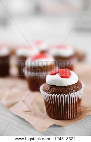 Cupcakes on craft paper on a light wooden background