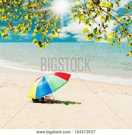Summer and travel concept Colorful umbrella with blue sea and white sand beach Can be use display and product