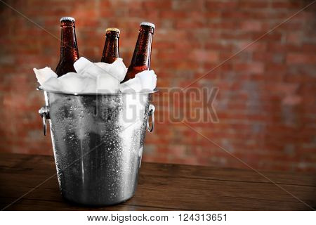 Brown glass bottles of beer in ice-pail on brick wall background