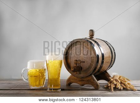 Beer barrel and glasses of beer with wheat on wooden table against grey background