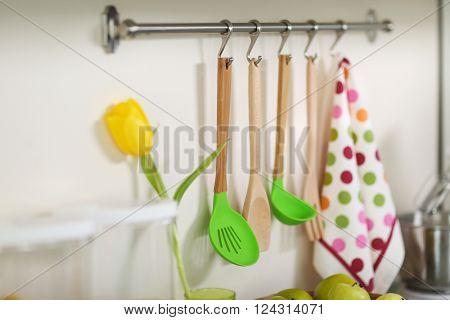 Set of wooden kitchen utensils and towel hanging on the wall
