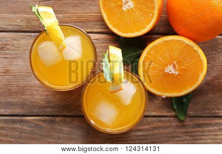 Two orange juices with ice and orange on wooden table background, view from above