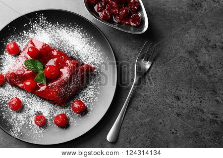 Powdered cherry strudel with mint on plate