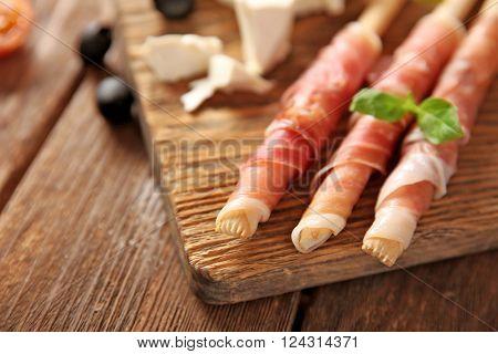 Bread sticks grissini with prosciutto ham on a  wooden board, close up