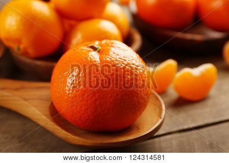 Peeled and unpeeled tangerines in wooden spoons and bowls, close up