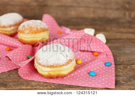 Delicious sugary donuts with pink napkin on wooden background