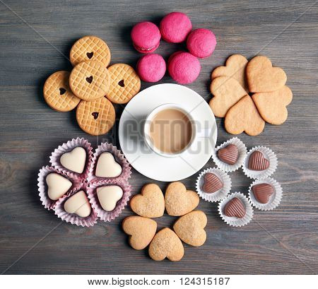 Valentine concept. Composition of cup, cookies and candies on blue background