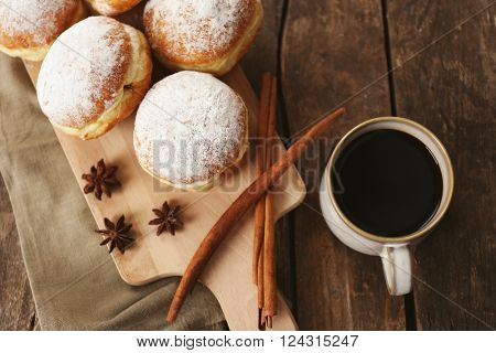 Delicious sugary donuts with spices and cup of coffee on wooden background