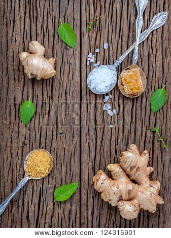 The ingredients of ginger tea with ginger roots , ginger powder , honey and peppermint on rustic wooden table.