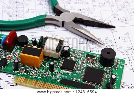 Printed circuit board with electrical components and precision tools lying on construction drawing of electronics, drawings and precision tools for engineer jobs, technology