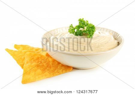 Ceramic bowl of tasty hummus with chips and parsley, isolated on white
