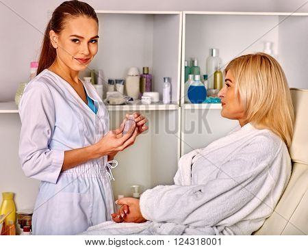 Woman middle-aged in spa salon with young beautician looking at camera.