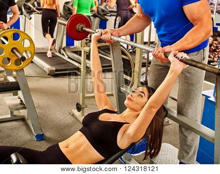 Woman with  thin waist working his arms and chest at gym. She lifting barbell.