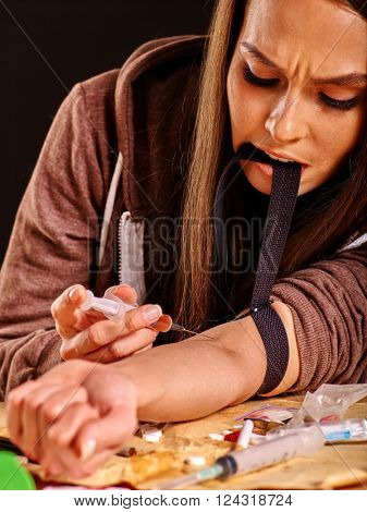 Female drug addict with  tourniquet on his arm and  syringe. Girl tightens a tourniquet teeth.