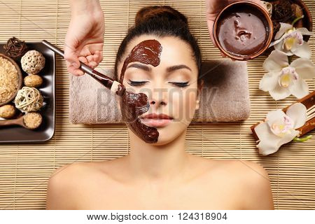 Beautiful young girl getting chocolate mask in spa salon