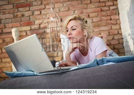 Young blonde woman using laptop computer, lying in bed.