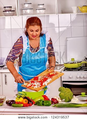 Mature woman with cutting board in blue apron preparing dinner at kitchen.