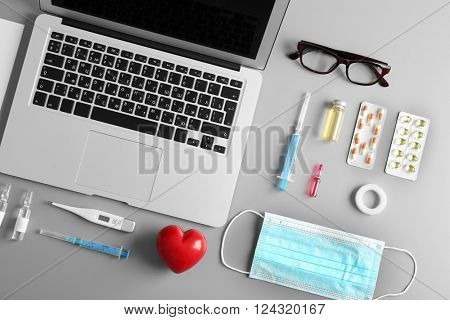 Doctor table with medicines, mask and laptop, top view