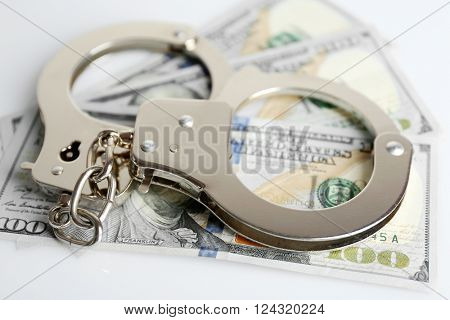 Handcuffs on dollar banknotes, close up. Corruption concept