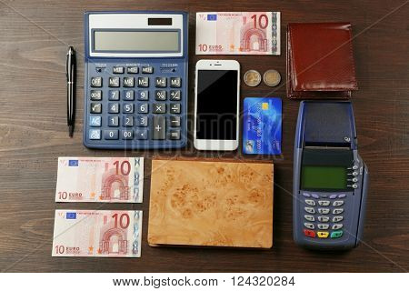 Credit card with card register and banknotes on wooden background