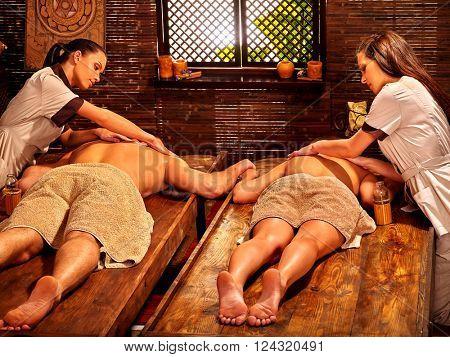 Couple  having oil Ayurveda spa treatment. Asian masseuse.