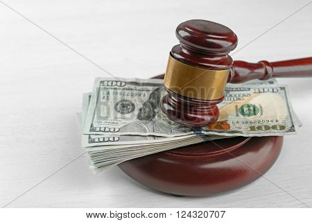 Law gavel with dollars isolated on white