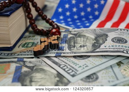 Holy Bible with rosary beads and American flag on money background