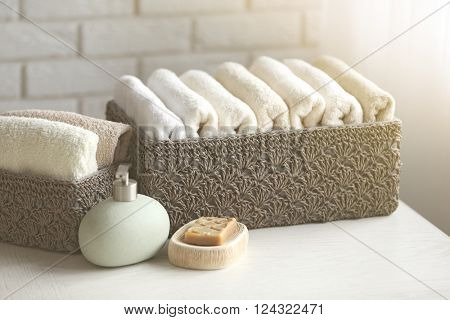 Wicker basket with towels inside and soap on wooden table background