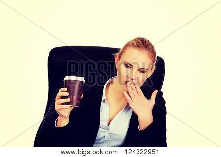 Yawning business woman sitting on wheel chair and holding cup of coffee