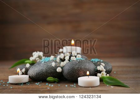 Spa still life with stones and candlelight on wooden background