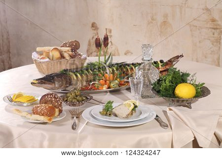 pike baked in the oven served with lemon and vegetables and vodka in pitcher