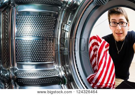 Funny men loading clothes to washing machine. From inside the washing machine view