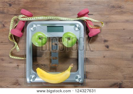 Healthy lifestyle concept. scales colored Apples measuring tape dumbbells banana look like face on wooden table