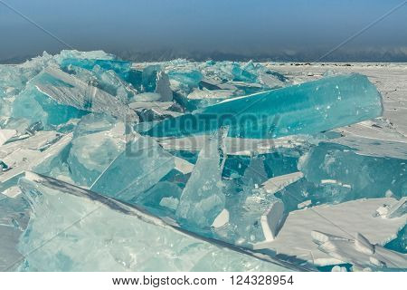 Clumps of blue ice on the snow. Beautiful winter landscape in the Lake Baikal.