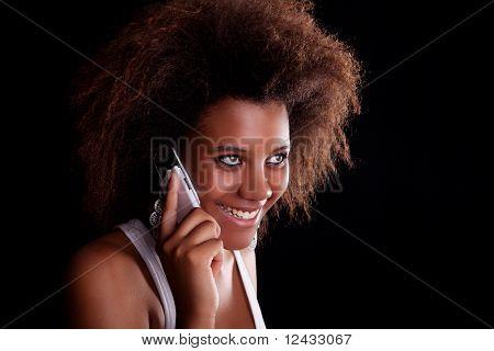 Bela mulher negra feliz no telefone, isolado no fundo preto. Studio Shot.