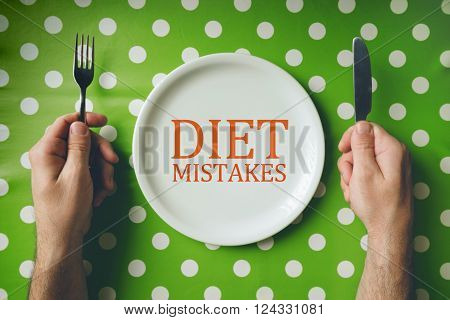 Diet mistakes concept top view of dinning table with male hands holding fork and knife over empty flat plate.