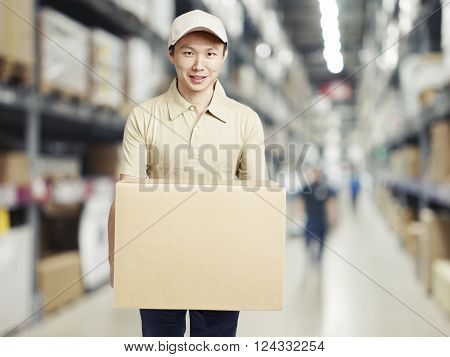 male warehouse worker carrying a carton box of goods in a cash and carry wholesale store.