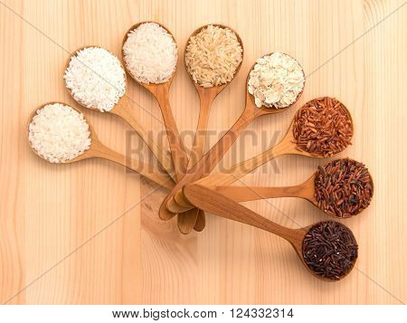 Thai cargo rice is the creation of the thai rice eaperts and Japanese Brown rice Glutionus Mixed whole grain traditional thai rices best rices for healthy in small wood spoon on a weathered driftwood background