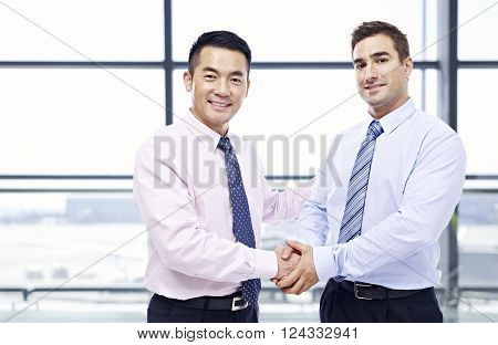 two businessmen one asian and one caucasian shaking hands looking at camera at modern airport.