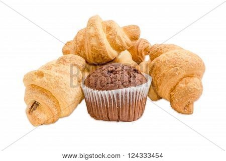 Several small croissant and sweet chocolate muffin in a paper cup on a light background